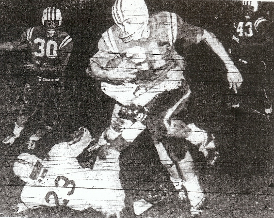 Crawford's Bill Rainey, all Southern California, is tackled by unidentified Kearny defender, while Don Henderrson (23), Jimmy Gilbert (30), and Larry Guske (43) are witnesses. Colts won San Diego Section title.
