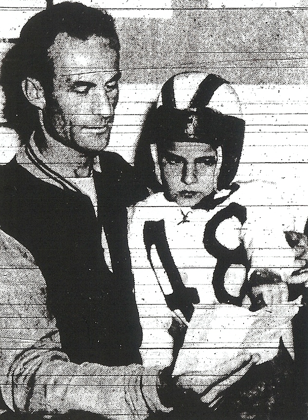Six-year-old Gary Bailey observes as his father, San Diego coach Bill Bailey, reads a 1945 telegram which stated that the Cavers were the No. 1-ranked team in the country.  Eleven years later the Baileys were on different sides.