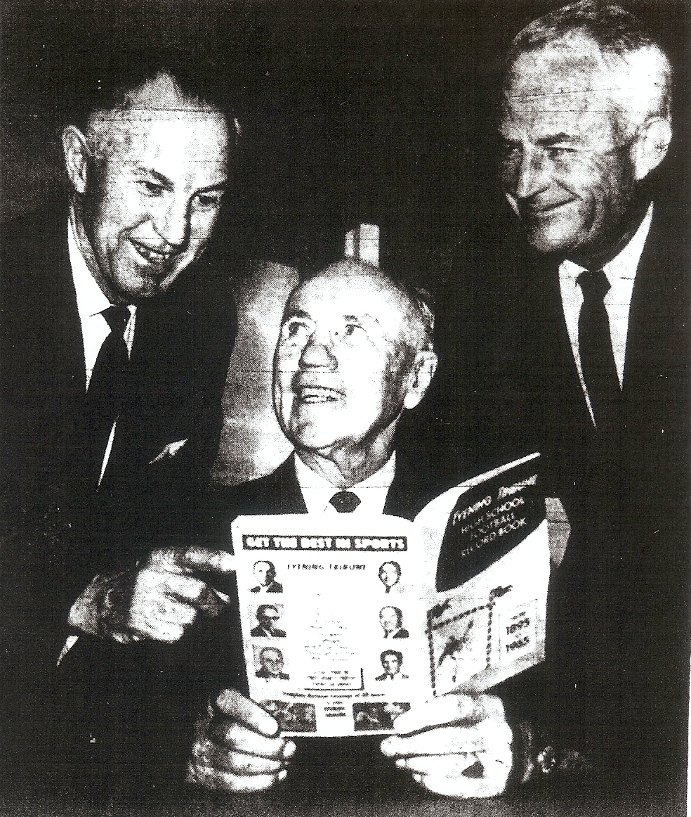 John Perry (left) joined retired coaches Jack Mashin (center) and Bill Bailey in perusing newly-published copy of Evening Tribune prep football record book in 1965.